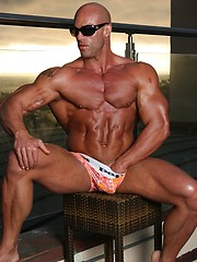 Bald athlete posing on a balcony