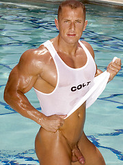 Muscle man posing by the pool