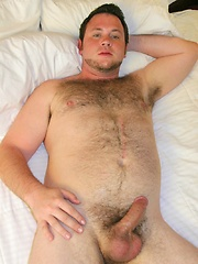 Young furry stud Sean Harte rolls around on the bed showing off his hairy ass and thick hard cock